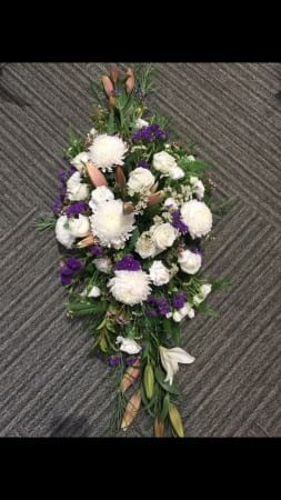 white and purple casket spray